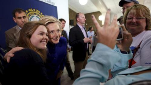 U.S. Democratic presidential candidate Hillary Clinton (2nd L) poses for a photograph with an audience member at a campaign town hall meeting in Claremont, New Hampshire August 11, 2015.   REUTERS/Brian Snyder