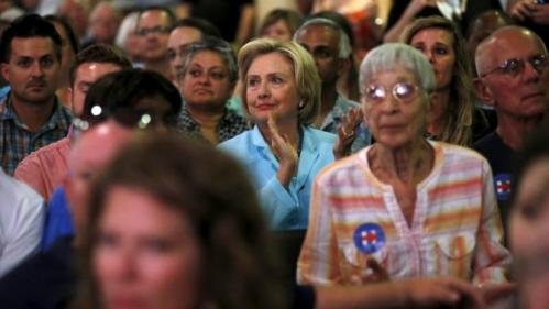 U.S. Democratic presidential candidate Hillary Clinton applauds a speaker as she sits among the attendees at the Iowa Democratic Wing Ding dinner in Clear Lake, Iowa, United States, August 14, 2015. REUTERS/Jim Young