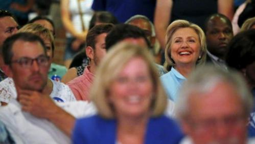 U.S. Democratic presidential candidate Hillary Clinton smiles as she sits among the attendees at the Iowa Democratic Wing Ding dinner in Clear Lake, Iowa, United States, August 14, 2015. REUTERS/Jim Young