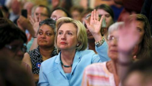 U.S. Democratic presidential candidate Hillary Clinton raises her hand to answer a question as she sits among the attendees at the Iowa Democratic Wing Ding dinner in Clear Lake, Iowa, United States, August 14, 2015. REUTERS/Jim Young