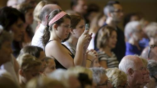 People listen as United States Democratic presidential candidate Hillary Clinton speaks about college affordability during a town hall meeting in Dubuque, Iowa August 14, 2015. REUTERS/Joshua Lott