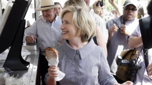 Democratic presidential candidate Hillary Rodham Clinton buys a pork chop during a visit to the Iowa State Fair, Saturday, Aug. 15, 2015, in Des Moines, Iowa. (AP Photo/Charlie Neibergall)