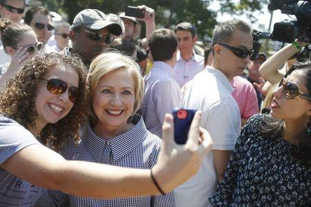 United States Democratic presidential candidate Hillary Clinton poses for a photo with a woman at the Iowa State Fair in Des Moines, Iowa August 15, 2015. REUTERS/Joshua Lott
