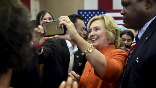 Democratic presidential candidate Hillary Clinton takes a photo with a supporter after speaking at a town hall meeting in Las Vegas, Nevada August 18, 2015. REUTERS/David Becker