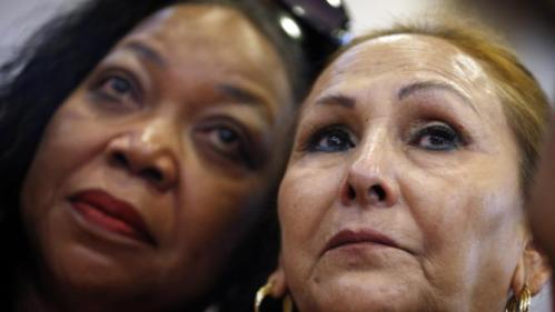Rosa Misner, right, cries as she and Juana Leia-Jordan, left, listen to Democratic presidential candidate Hillary Rodham Clinton speak at a town hall meeting Tuesday, Aug. 18, 2015, in North Las Vegas, Nev. (AP Photo/John Locher)