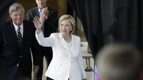 Democratic presidential candidate Hillary Rodham Clinton, followed by Agriculture Secretary Tom Vilsack, left, waves before she speaks about rural issues at the Des Moines Area Community College, Wednesday, Aug. 26, 2015, in Ankeny, Iowa. (AP Photo/Charlie Neibergall)