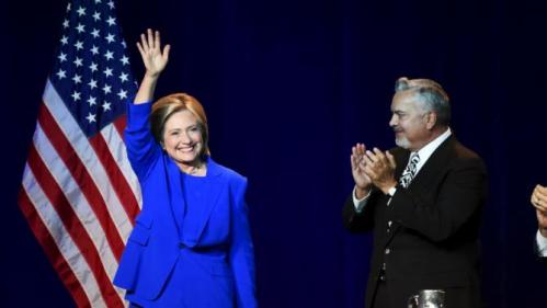 Democratic presidential candidate Hillary Clinton (L) waves to the crowd after addressing the Democratic National Committee (DNC) Summer Meeting as Henry Munoz, National Finance Chair, looks on in Minneapolis, Minnesota, August 28, 2015. REUTERS/Craig Lassig