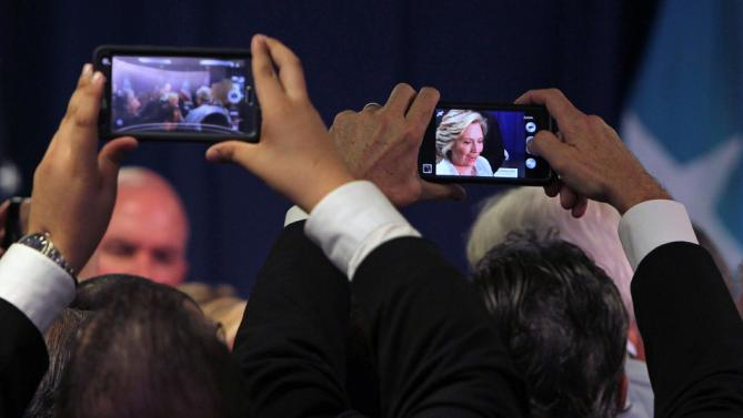 Supporters use their phones to make a photo of Democratic presidential candidate Hillary Rodham Clinton as she speaks at a news conference after a health care roundtable, in San Juan, Puerto Rico, Friday, Sept. 4, 2015. Clinton, who won Puerto Rico's 2008 Democratic primary election, defended her support for giving Puerto Rico bankruptcy protection during a round-table discussion focused on the island's health-care problems. (AP Photo/Ricardo Arduengo)
