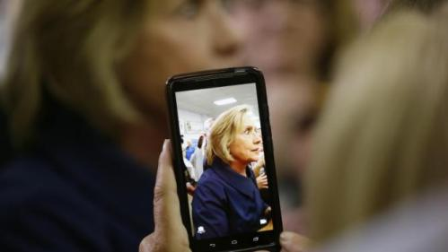 Democratic presidential candidate Hillary Rodham Clinton is seen on a phone as she greets supporters during the Annual Hawkeye Labor Council AFL-CIO Labor Day picnic, Monday, Sept. 7, 2015, in Cedar Rapids, Iowa. (AP Photo/Charlie Neibergall)