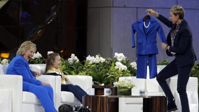 Democratic presidential candidate Hillary Rodham Clinton, left, and, 5-year old Presidential expert Macey Hensley, center, react as Ellen DeGeneres presents Macey with a pant suit like Hillary's during a taping of The Ellen DeGeneres Show, Tuesday, Sept. 8, 2015, at Rockefeller Center in New York. (AP Photo/Mary Altaffer)