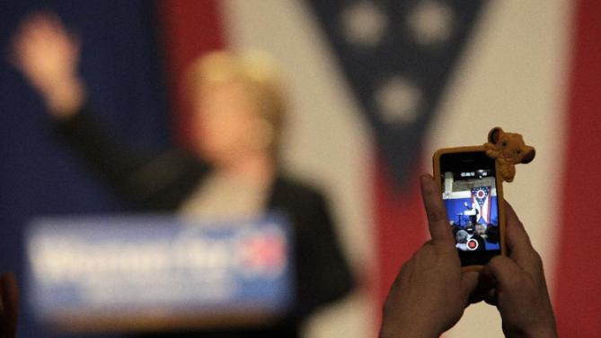 A person in the crowd takes a photo of Democratic presidential candidate Hillary Rodham Clinton as speaks during a 'Women for Hillary' grassroots organizing meeting, Thursday, Sept. 10, 2015, in Columbus, Ohio. (AP Photo/Jay LaPrete)