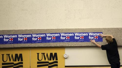 "A man puts up ""Woman for Hillary"" signs before Democratic presidential candidate Hillary Clinton speaks at a meeting in Milwaukee, Wisconsin September 10, 2015. REUTERS/Darren Hauck"