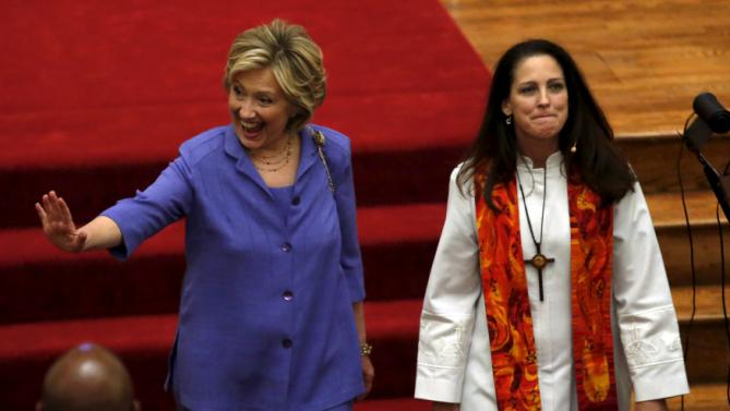 U.S. Democratic presidential candidate Hillary Clinton waves as she leaves with Senior Pastor Ginger Gaines-Cirelli after the Foundry United Methodist Church's bicentennial service in Washington September 13, 2015. REUTERS/Yuri Gripas