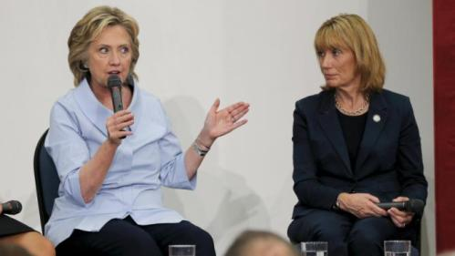 New Hampshire Governor Maggie Hassan (R) listens as U.S. Democratic presidential candidate Hillary Clinton answers a question from the audience at a campaign community forum on college affordability in Durham, New Hampshire September 18, 2015. Governor Hassan announced her endorsement of Clinton at the event. REUTERS/Brian Snyder