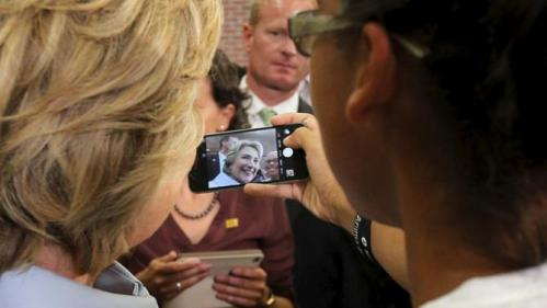 U.S. Democratic presidential candidate Hillary Clinton poses for a selfie with an audience member at a campaign community forum on college affordability in Durham, New Hampshire September 18, 2015. REUTERS/Brian Snyder