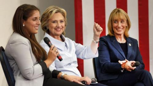 Democratic presidential candidate Hillary Rodham Clinton, center, accompanied by New Hampshire Gov. Maggie Hassan, right, reacts as she listens to student Stacy Horne, left, during a campaign stop at the University of New Hampshire, Friday, Sept. 18, 2015, in Durham, N.H. (AP Photo/Jim Cole)