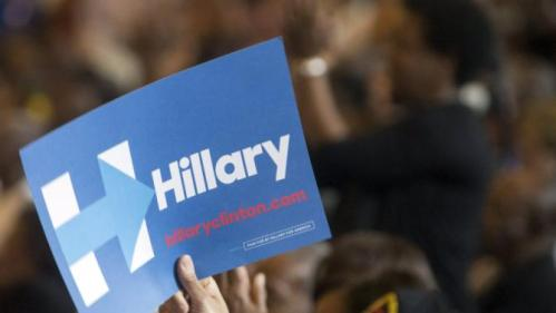 A supporter waves a sign for U.S. Democratic presidential candidate Hillary Clinton while Clinton speaks to a grassroots organizing meeting at the Louisiana Leadership Institute in Baton Rouge, Louisiana, September 21, 2015. REUTERS/Lee Celano