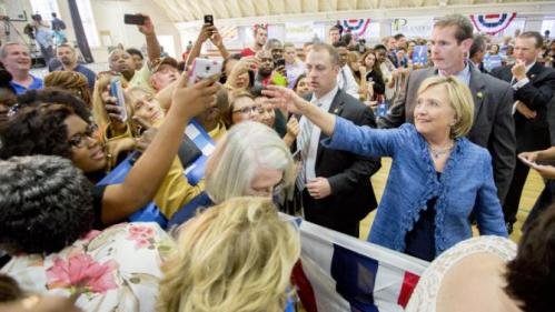 Democratic presidential candidate Hillary Rodham Clinton reaches for a phone to take a photo with attendees at a grassroots organizing meeting at Philander Smith College Monday, Sept. 21, 2015, in Little Rock, Ark. (AP Photo/Gareth Patterson)