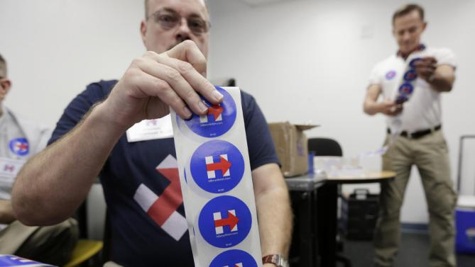 Volunteer Gary Hensley of Pompano Beach, Fla., prepares campaign stickers before a campaign event by Democratic presidential candidate Hillary Rodham Clinton, Friday, Oct. 2, 2015, at Broward College in Davie, Fla. (AP Photo/Lynne Sladky)