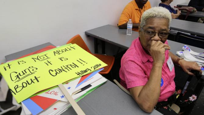 A volunteer sits by a campaign sign stating support of gun control before an event by Democratic presidential candidate Hillary Rodham Clinton, Friday, Oct. 2, 2015, at Broward College in Davie, Fla. (AP Photo/Lynne Sladky)