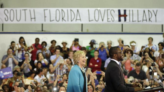 Democratic presidential candidate Hillary Rodham Clinton is introduced by honors student Darnell Joseph, 18, right, before speaking at a campaign event at Broward College, Friday, Oct. 2, 2015, in Davie, Fla. (AP Photo/Lynne Sladky)