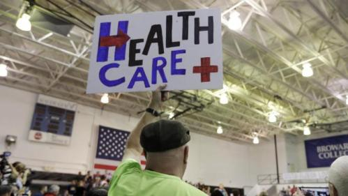 A supporter of Democratic presidential candidate Hillary Rodham Clinton holds up a sign in favor of health care as Clinton speaks during a campaign event at Broward College, Friday, Oct. 2, 2015, in Davie, Fla. (AP Photo/Lynne Sladky)