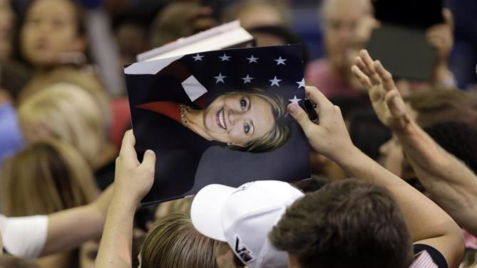 Supporters hold a photo of Democratic presidential candidate Hillary Rodham Clinton hoping to get it autographed following a speech by Clinton at a campaign event at Broward College, Friday, Oct. 2, 2015, in Davie, Fla. (AP Photo/Lynne Sladky)