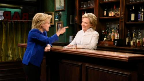 "In this Saturday, Oct. 3, 2015, photo, provided by NBC, Kate McKinnon, left, portraying Hillary Rodham Clinton, and Hillary Rodham Clinton, right, portraying Val, appear during the ""Bar Talk"" sketch on ""Saturday Night Live,"" in New York. (Dana Edelson/NBC via AP)"