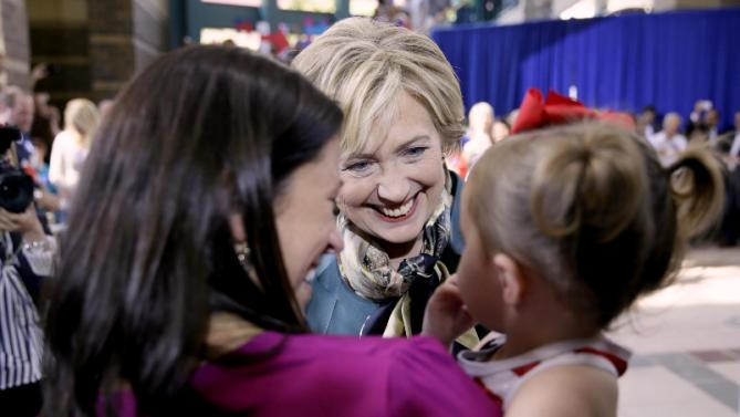 Democratic presidential candidate Hillary Rodham Clinton talks with Kandis Bower of Davenport, Iowa, and her 2-year old daughter Jaida before a community forum, Tuesday, Oct. 6, 2015, in Davenport, Iowa. (AP Photo/Charlie Neibergall)