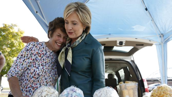 U.S. Democratic presidential candidate Hillary Clinton hugs a vendor as she shops at a farmer's market in Davenport, Iowa October 6, 2015.    REUTERS/Jim Young