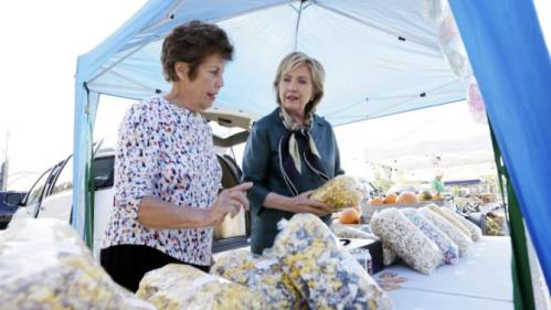 Democratic presidential candidate Hillary Rodham Clinton buys kettle corn from vendor Nancy Remrey during a visit to the downtown Davenport Farmers Market, Tuesday, Oct. 6, 2015, in Davenport, Iowa. (AP Photo/Charlie Neibergall)