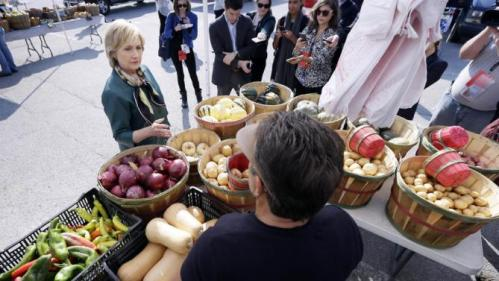 Democratic presidential candidate Hillary Rodham Clinton talks with a vendor during a visit to the downtown Davenport Farmers Market, Tuesday, Oct. 6, 2015, in Davenport, Iowa. (AP Photo/Charlie Neibergall)