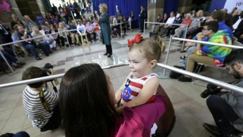 Kandis Bower, of Davenport, Iowa, holds her 2-year old daughter Jaida as they listen to Democratic presidential candidate Hillary Rodham Clinton speak during a community forum, Tuesday, Oct. 6, 2015, in Davenport, Iowa. (AP Photo/Charlie Neibergall)