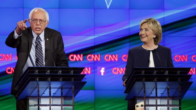 Sen. Bernie Sanders, of Vermont, left, speaks as Hillary Rodham Clinton looks on during the CNN Democratic presidential debate Tuesday, Oct. 13, 2015, in Las Vegas. (AP Photo/John Locher)