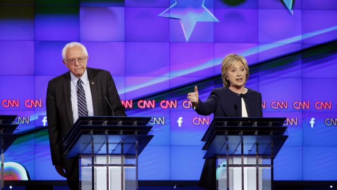 Hillary Rodham Clinton, right, speaks as Sen. Bernie Sanders, of Vermont, looks on during the CNN Democratic presidential debate Tuesday, Oct. 13, 2015, in Las Vegas. (AP Photo/John Locher)