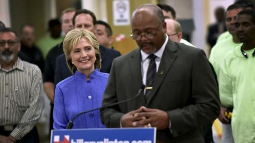 Democratic U.S. presidential candidate Hillary Clinton smiles as she receives an endorsement from the International Union of Painters and Allied Trades President Kenneth Rigmaiden (R) during a visit to an IUPAT training center in Las Vegas, Nevada October 14, 2015. REUTERS/David Becker