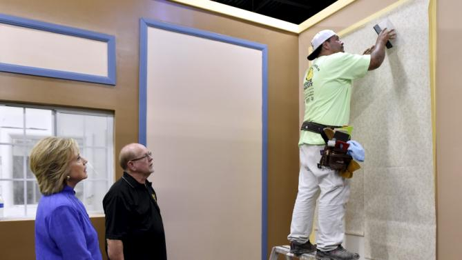 Democratic U.S. presidential candidate Hillary Clinton (L) looks on as instructor Marvin Alexander (C) watches over union apprentice Luis Rodriguez hang wallpaper during a visit to the International Union of Painters and Allied Trades (IUPAT) training center in Las Vegas, Nevada October 14, 2015. REUTERS/David Becker
