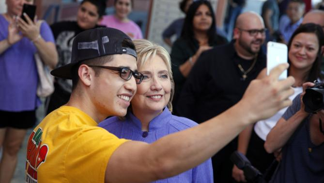 Democratic presidential candidate Hillary Rodham Clinton poses for a selfie while stopping for ice cream Wednesday, Oct. 14, 2015, in North Las Vegas, Nev. Clinton made a stop for ice cream with her staff and posed for pictures with people. (AP Photo/John Locher)