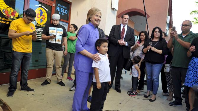 Democratic U.S. presidential candidate Hillary Clinton poses with a boy after stopping for ice cream in North Las Vegas, Nevada, October 14, 2015. REUTERS/David Becker