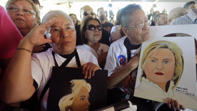 Esther Alvarado, left, and Maria Anita Monsivaiz, right, hold portraits they created of Democratic presidential candidate Hillary Rodham Clinton during a campaign event, Thursday, Oct. 15, 2015, in San Antonio. (AP Photo/Eric Gay)