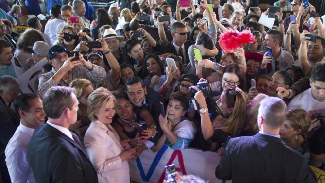 "Democratic U.S. presidential candidate Hillary Clinton greets the crowd  with U.S. Secretary of Housing and Urban Development Julian Castro (FarL) during a ""Latinos for Hillary"" rally in San Antonio, Texas October 15, 2015. Castro endorsed Clinton's campaign for president. REUTERS/Darren Abate"