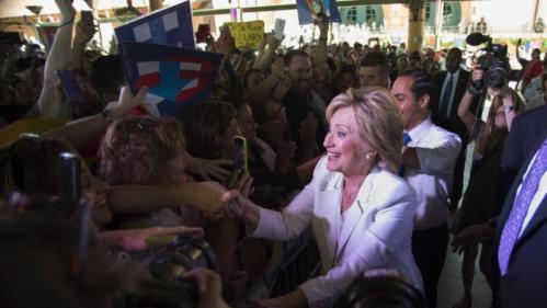 """Democratic U.S. presidential candidate Hillary Clinton greets supporters with U.S. Department of Housing and Urban Development Secretary Julian Castro (R-rear) at her side at the conclusion of a """"Latinos for Hillary"""" rally in San Antonio, Texas October 15, 2015. REUTERS/Darren Abate"""