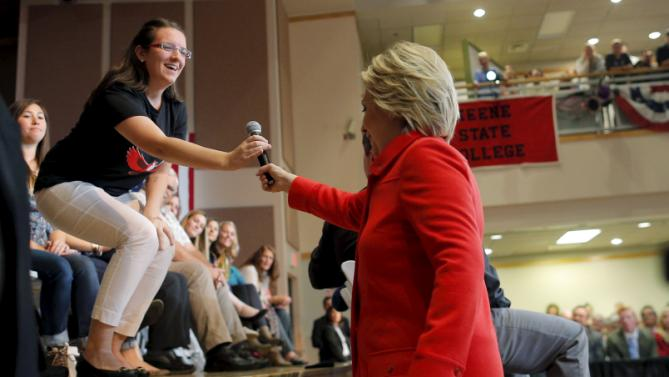 U.S. Democratic presidential candidate Hillary Clinton hands her microphone to an audience member for a question at a campaign town hall meeting in Keene, New Hampshire October 16, 2015. REUTERS/Brian Snyder