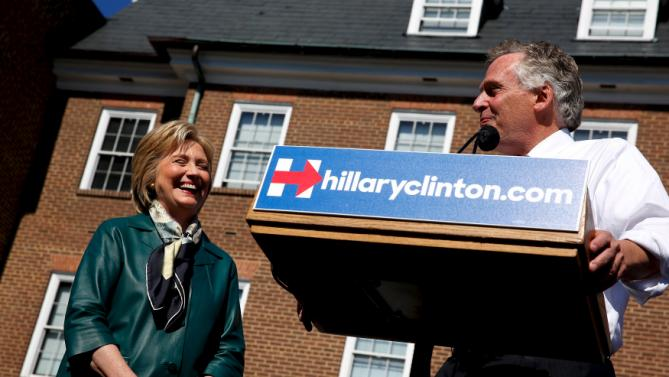 Democratic presidential candidate Hillary Clinton (L) is introduced by Virginia Governor Terry McAuliffe (R) as she takes the stage for a rally with grassroots supporters in Alexandria, Virginia, October 23, 2015. REUTERS/Jonathan Ernst