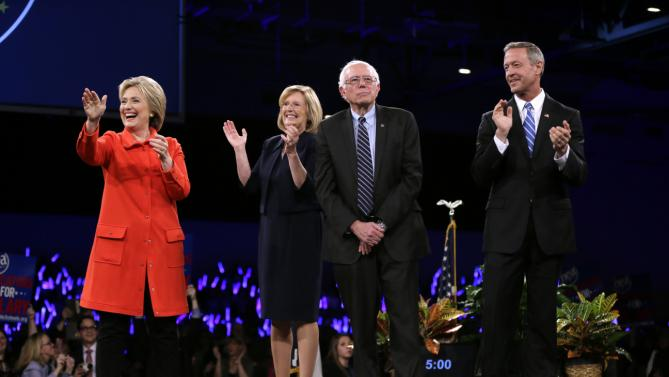 Democratic presidential candidates Hillary Rodham Clinton, left, Sen. Bernie Sanders, I-Vt., second from right, and former Maryland Gov. Martin O'Malley, right, stand on stage together at the start of the Iowa Democratic Party's Jefferson-Jackson Dinner, Saturday, Oct. 24, 2015, in Des Moines, Iowa. Iowa Democratic Party chair Andy McGuire, second from left, looks on. (AP Photo/Charlie Neibergall)