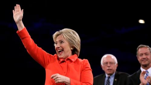 Democratic presidential candidate Hillary Rodham Clinton waves to supporters during the Iowa Democratic Party's Jefferson-Jackson Dinner, Saturday, Oct. 24, 2015, in Des Moines, Iowa. Democratic presidential candidates Sen. Bernie Sanders, I-Vt., center, and former Maryland Gov. Martin O'Malley, right, look on. (AP Photo/Charlie Neibergall)
