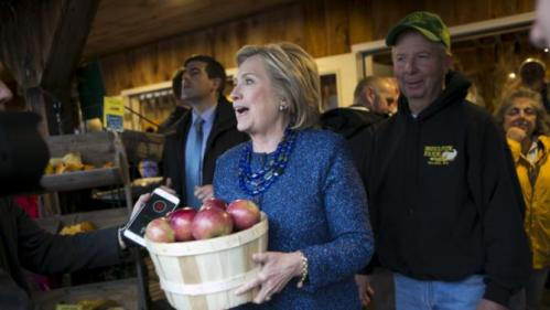 U.S. Democratic presidential candidate and former Secretary of State Hillary Clinton holds a basket of apples at Moulton Farm in Meredith, New Hampshire October 28, 2015. REUTERS/Katherine Taylor