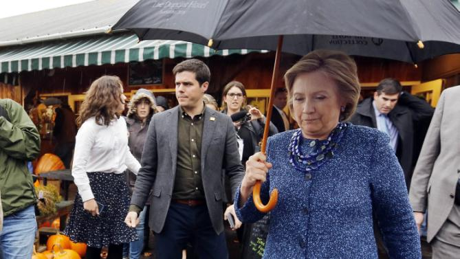 Democratic presidential candidate Hillary Rodham Clinton walks through the rain after a campaign stop at the Moulton Farm Wednesday, Oct. 28, 2015, in Meredith, N.H. (AP Photo/Jim Cole)
