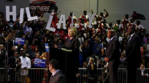 "U.S. Democratic presidential candidate Hillary Clinton receives support from U.S. Congressman John Lewis (2nd R) and Atlanta mayor Kasim Reed (R) as she is interrupted by protesters at the ""African Americans for Hillary"" rally at Clark Atlanta University in Atlanta, Georgia October 30 2015. REUTERS/Tami Chappell"