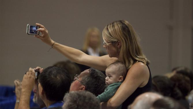 A supporter holds her child while taking a photo as U.S. Democratic presidential candidate Hillary Clinton speaks to members of The International Longshoremen's Association in Charleston, South Carolina, October 31, 2015.  REUTERS/Randall Hill